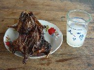 Plate with roast and glass of palm beer